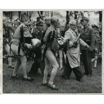 1956 Press Photo Knight trapped in bent armor carried off jousting field