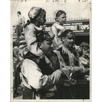 1954 Press Photo Costumed kids ride on shoulders for better views at Mardi Gras