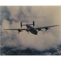 1996 Press Photo Plane Flying Over a Unknown City in Clouds