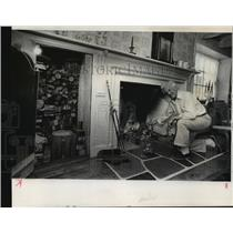 1978 Press Photo Oliver Winter knelt at the fireplace of his 1850 log house.