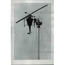 1965 Press Photo Harry Johansen step out from a helicopter to a steeple