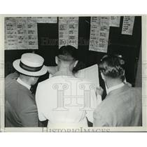 1939 Press Photo Men at racetrack betting with score sheets - net33611