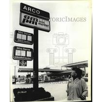 1980 Press Photo Chris Conpors stands by the Oregon Service station signage