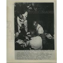 1964 Press Photo Dr. Lash Knox examines personal effects from plane crash