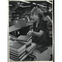 1982 Press Photo Goodwill employee Maureen Whitney sorts book from conveyor