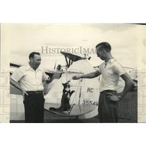 Press Photo Patrolmen playing with a cat standing on the plane at Hanford