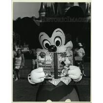 "1986 Press Photo Mickey Mouse Reads ""Cooking with Mickey Around the World"""