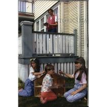 1993 Press Photo Mother reads while watching her daughters play with doll house
