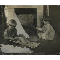 1919 Press Photo Two small children play in front of a home fireplace