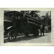 1930 Press Photo Man standing next to logs piled on truck, Colville, Washington
