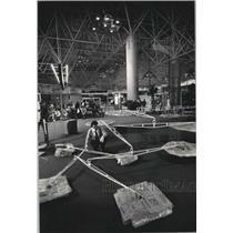 1987 Press Photo Michael Lord Placing Alexander Calder Artwork, Mitchell Airport