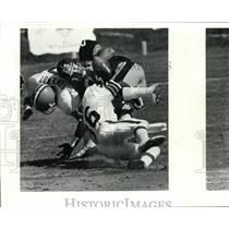 1987 Press Photo Lupe Sanchez fumbles the ball after being hit by Stephen Braggs