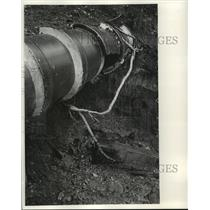 1970 Press Photo Fluid drains from large hole in pipe, pollution