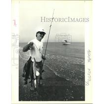 "1991 Press Photo Ocean fisherman holds up his ""catch of the day."" - nob08877"