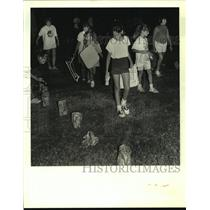 1988 Press Photo Girl Scouts walk through alley of lanterns they made earlier.