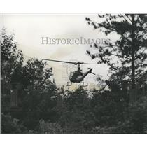 1975 Press Photo Helicopter searches thickly wooded area where bandits fled