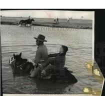 1955 Press Photo A boy held on as a horse forded water that blocked the path