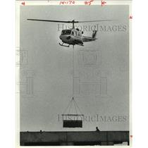 1980 Press Photo Helicopter lifts air conditioner on top of Briar Park Bldg, TX
