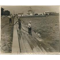 1962 Press Photo Workers washing down the dead fish at lakeside. - nob54280