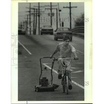1991 Press Photo Greg Gaines towing mower while riding his bike - nob54776