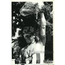 1990 Press Photo Unidentifed woman raises flowers after winning bicycle race
