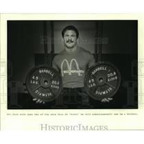 1985 Press Photo Weightlifter Jim Cash holds two 45 pound barbell disks.