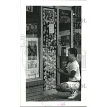 1992 Press Photo Tuyen Dang covers store door with Texas lottery tickets