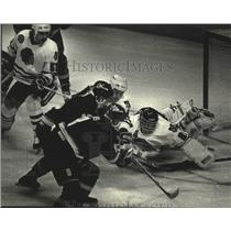 1990 Press Photo Vancouver hockey's Greg Adams slides puck past opponent