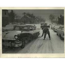 1962 Press Photo City worker Fred Bublitz shovels salt under wheels of stuck car