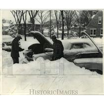 1962 Press Photo Wauwatosa neighbors try to jump start car in the snow and cold.