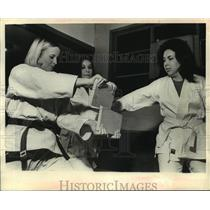 1970 Press Photo Group of women using Karate skills to break wooden planks.