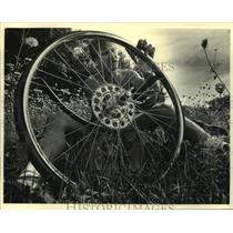 1987 Press Photo Mark Biederwolf repairing friends bicycle on the SAAGBRAW.