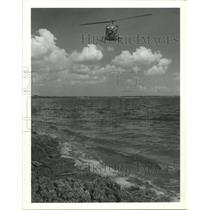 1988 Press Photo Helicopter over water; spray for mosquitoes in Houston
