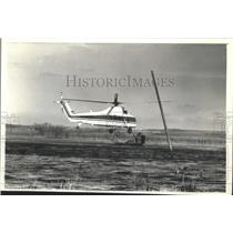 1990 Press Photo Helicopter hovers over water near Horizon Marsh's island