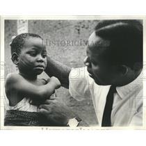 1963 Press Photo Rockefeller Foundation Doctor Examining Little Girl in Nigeria