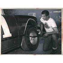 1964 Press Photo Tom Egret Changing Tire On Car