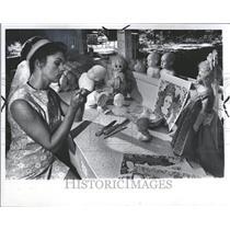 1965 Press Photo Woman Sculpts Baby Dolls Painter