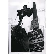 1970 Press Photo Carmen Pastor on signpost waits to see parade on his unicycle