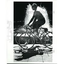 1983 Press Photo Bicyclist Riding by a Fountain