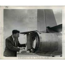 1954 Press Photo A engerneer with a device to slow a airplane's roll.
