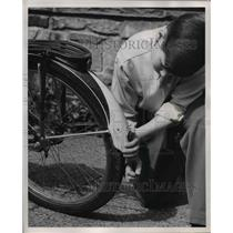 1951 Press Photo Boy Checks Bike for Light and Tail Reflector