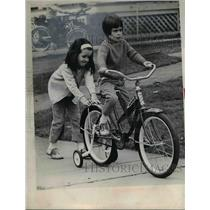1968 Press Photo Bunnie Bosworth and Raelynne Konschak play with the bike