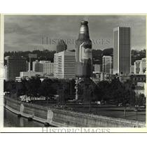 1984 Press Photo Bottle Shaped hot air balloon seems larger than buildings.