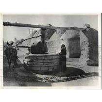 1935 Press Photo Inhabitants in Syrian desert village grind millet for bread