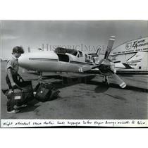 1985 Press Photo Flight attendant Steve Martini loads baggage for Empire Airways