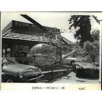 1986 Press Photo Larry Stearns, owner of Park Avenue Motors, adjusts banner.