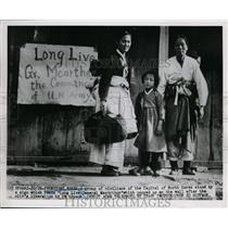 1950 Press Photo Family stands next to sign post city liberation In Pyongyang