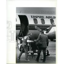 1989 Press Photo Empire Airlines employee Ken Watson helps passengers on flight.