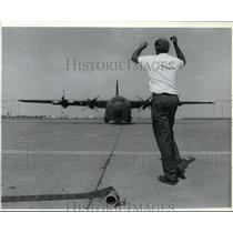 1988 Press Photo Brian Helwig directs a C-130 toward a hangar at Geiger Field