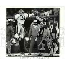 1986 Press Photo Frank Minnifield goes up with Dolphins receiver Mark Clayton